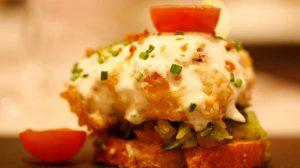 Gratinado de queso relleno de arroz sobre cama de verduras